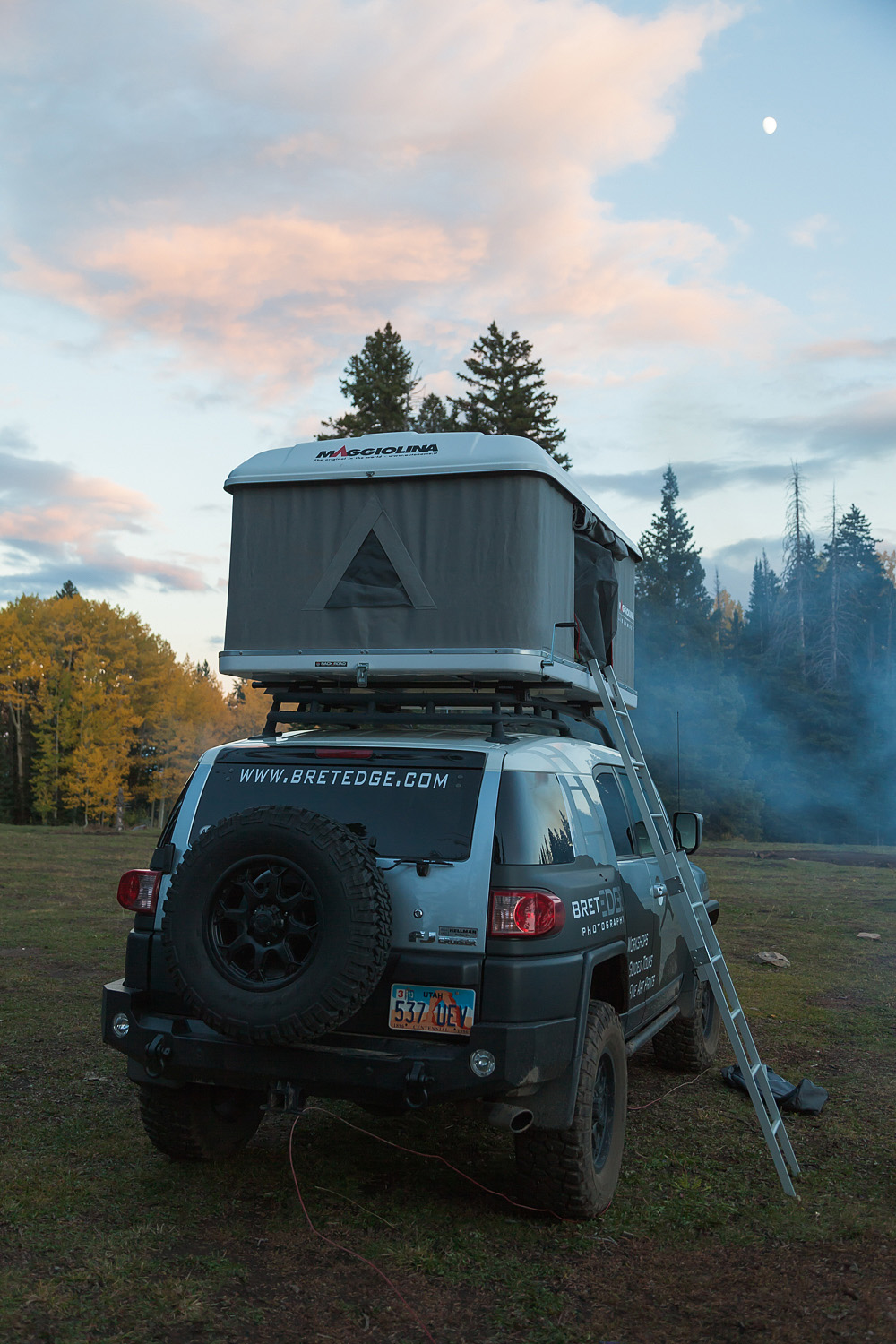A Toyota FJ Cruiser with a Maggiolina roof top tent deployed is parked near Medicine Lake & Overlanding Adventures and Photography | Expedition One